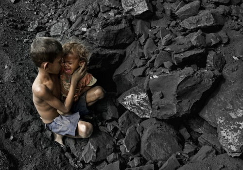 Brothers #2 by Parth Pratim Saha. The children living near opencast coal mining sites are affected by acute and chronic respiratory health. Elder brother is caring his ailing brother in such a coal mine area.