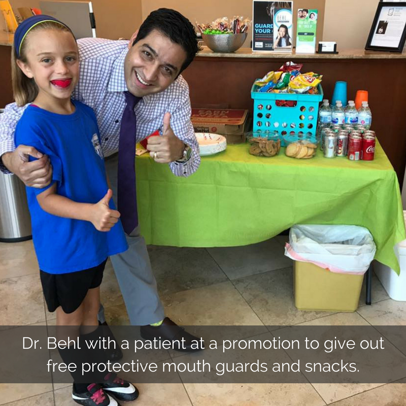 dr-behl-with-patient-at-a-promotion-to-give-out-free-protective-mouth-guards-and-snacks